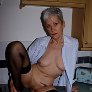 GILF teasing and showing in the kitchen flashing her body