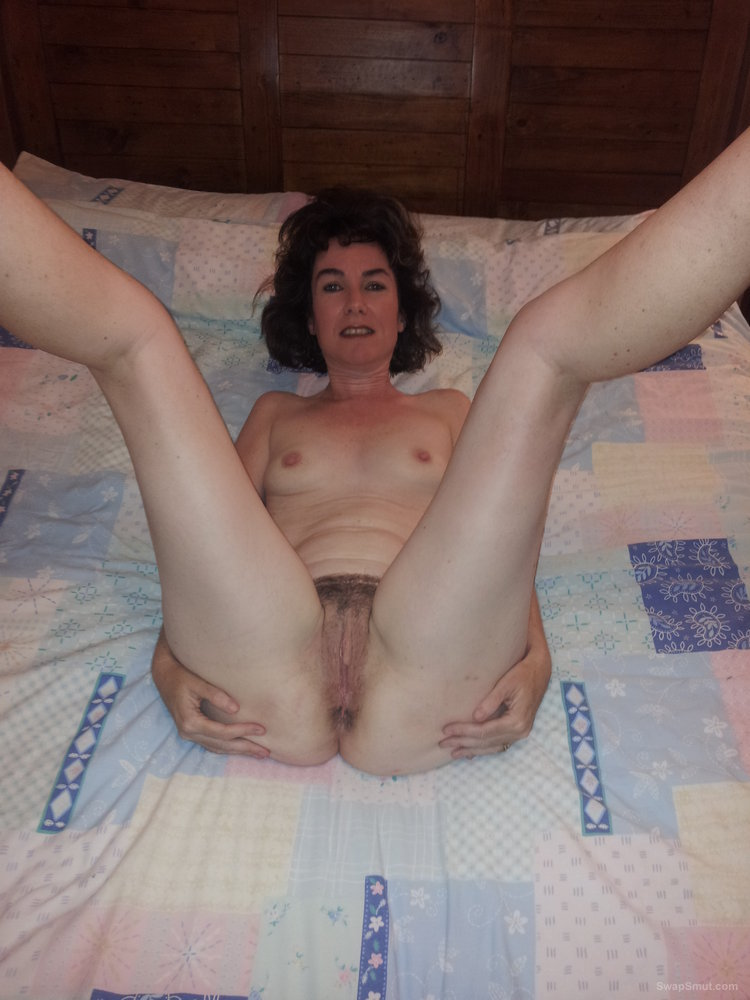 Wife at home on bed spreading legs showing pussy