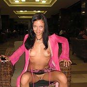 Dark haired beauty flashing in hotel lobby