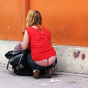 Young lady with beautiful panty less bum searching for something in her bag on the street
