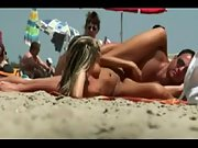 Wonderful blonde babe gets caught playing with her man's dong at the nudist beach